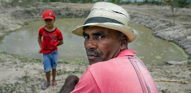 O agricultor Jovenito José dos Reis e seu neto, Carlos Henrique, em frente ao tanque que escavou em seu sítio no povoado de Boqueirão, em Santa Bárbara (BA), cidade que decretou situação de emergência por causa da seca que já dura cinco anos na região