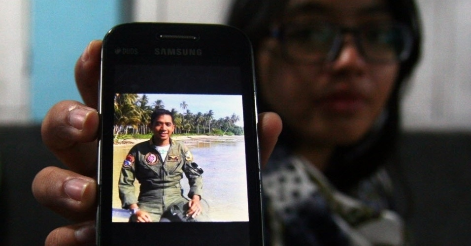 30.jun.2015 - Familiar exibe foto do capitão da Força Aérea indonésia Sandy Permana, membro da tripulação a bordo da aeronave C-130 Hercules que caiu em Medan, no norte de Sumatra. O acidente incendiou casas e veículos e matou mais de cem pessoas