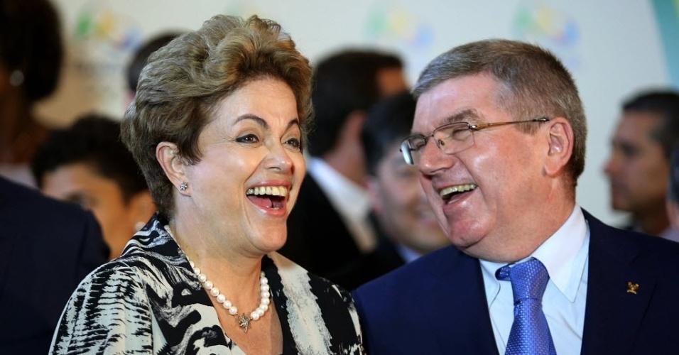 5.ago.2015 - Presidente Dilma Rousseff solta uma risada ao lado do presidente do COI (Comitê Olímpico Internacional), Thomas Bach. No evento para iniciar a contagem regressiva para a Olimpíada no Rio, Bach elogiou a preparação cidade para Jogos Olímpicos