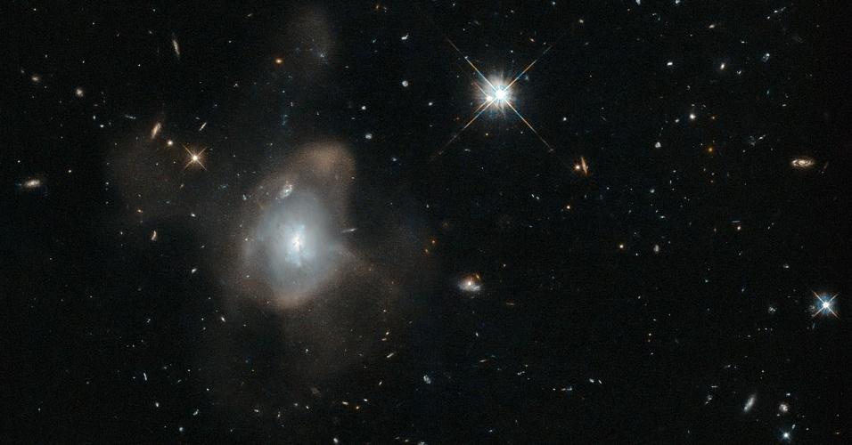 25.nov.2015 - DANÇA NO ESPAÇO - Uma galáxia curiosa, oficialmente conhecida por 2MASX J16270254+4328340, foi fotografada pelo telescópio espacial Hubble fazendo a
