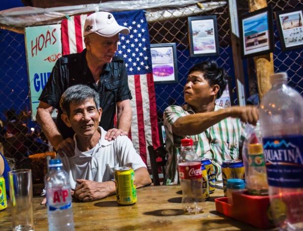 Nguyen Tien (sentado, à esq.), ex-soldado vietcongue que perdeu uma perna na guerra contra os EUA, confraterniza com Larry Vetter (em pé), veterano norte-americano