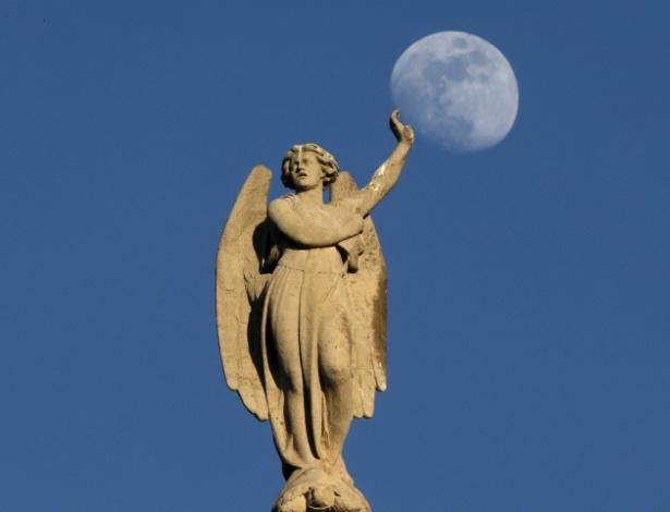 18.abr.2016 - Estátua da igreja de Saint-Germain l'Auxerrois 'segura' lua em Paris, na França