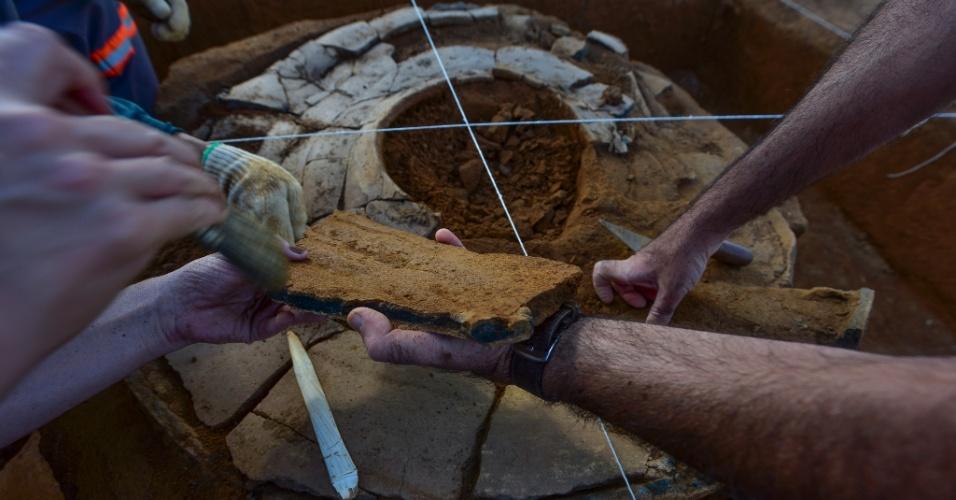 22.abr.2016 - Arqueólogos estudam tampa de urna funerária em sítio arqueológico, em São José dos Campos, em São Paulo. A peça foi encontrada em local pertencente a tribo tupi-guarani