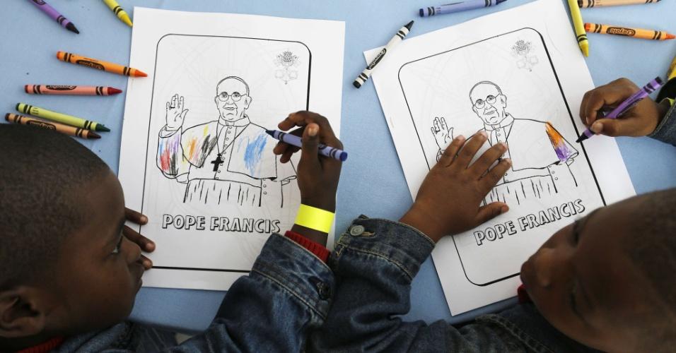 24.set.2015 - Kaydn Dorsey (à esq.) e Lionel Perkins pintam desenhos com imagem do papa Francisco enquanto esperam por sua visita à Arquidiocese de Washington