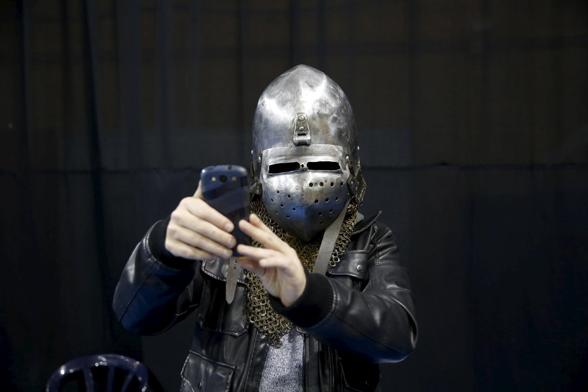 23.jan.2016 - Olha que choque de tecnologias: um homem vestido com casaco de couro e um capacete que remete a períodos mais antigos tira uma selfie com o seu smartphone durante o torneio em Israel