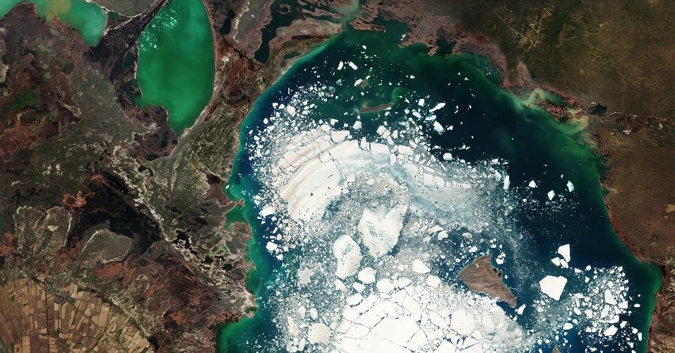 """23.set.2016 - Grandes pedaços de gelo flutuam no lago Alakol, no Cazaquistão. A água do lago de sal congela por dois meses no inverno e derrete na primavera. Alakol significa """"lago multicolorida"""". Podemos ver na imagem feita pelo satélite Copernicus Sentinel-2 vários tons de verde e azul, que variam dependendo da profundidade, de sedimentos e do fitoplâncton. Os dois lagos menores no alto do lado esquerdo da foto são Kosharkol e Sasykkol. O lago é considerado rico em minerais, e sua lama é utilizada por turistas como terapêutica. A região tem solo fértil, com desenvolvimento de agricultura nas margens, e recebe aves migratórias"""