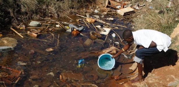 Homem coleta água em lugar sem tratamento em Harare, capital do Zimbábue