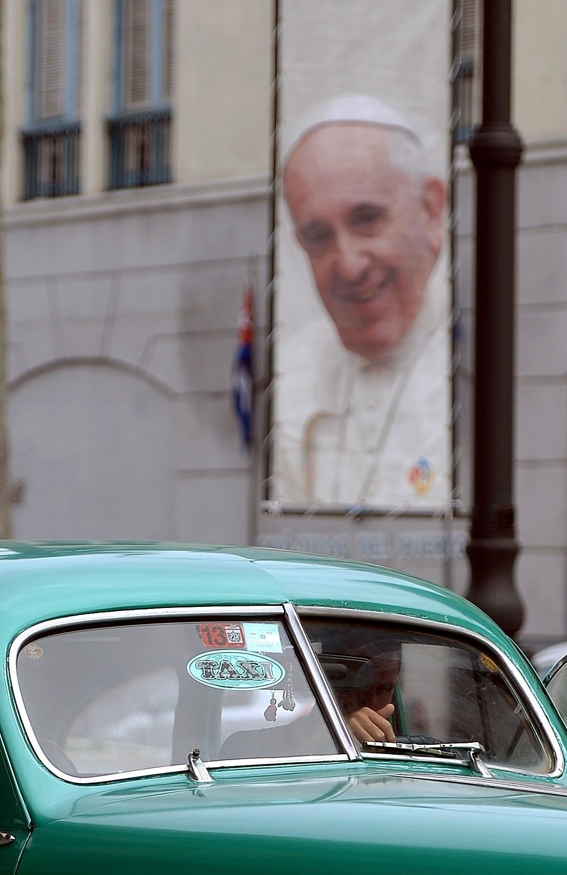 17.set.2015 - Motorista de taxi conduz seu veículo ao lado de um pôster do papa Francisco em uma rua de Havana, Cuba,  anunciando a visita do pontífice ao país. O papa Francisco começará no próximo sábado (19) sua 10ª viagem internacional, um périplo que o levará a Cuba e aos Estados Unidos durante nove dias, nos quais fará 26 discursos
