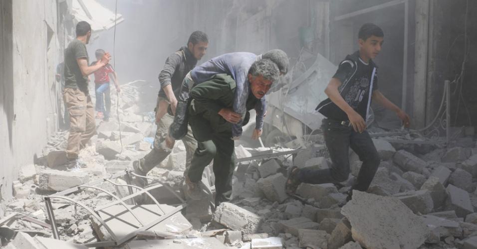 29.abr.2016 - Sírios avacuam edifícios destruídos na sequência de um ataque aéreo em bairro controlado pelos rebeldes da Al-Qatarji, em Aleppo, Síria. Um dia antes, o último médico pediatra que havia na região morreu depois de bombardeio num hospital da cidade
