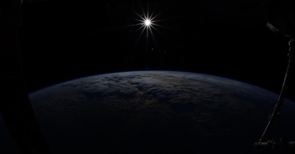 10.dez.2015 - Fotografia impressionante do astronauta Kjell Lindgren, em seu último dia na Estação Espacial Internacional, mostra a Terra vista do Espaço. Em meio a escuridão, uma estrela ilumina parte do planeta: