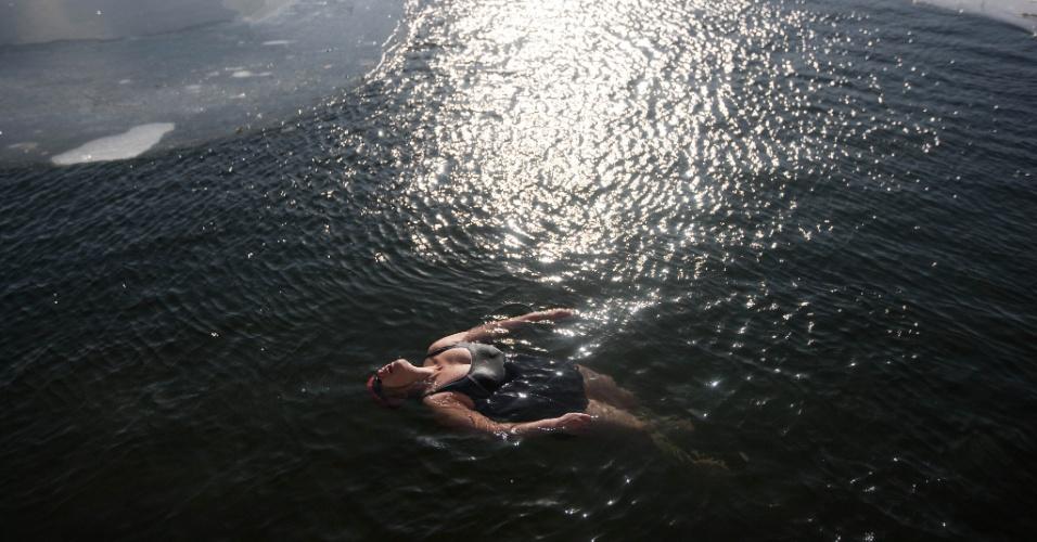 23.jan.2016 - Uma mulher que gosta de águas geladas mergulha em um lago parcialmente congelado de Pequim, na China. A máxima em Pequim foi de -10º C, mas isso não intimidou a moça