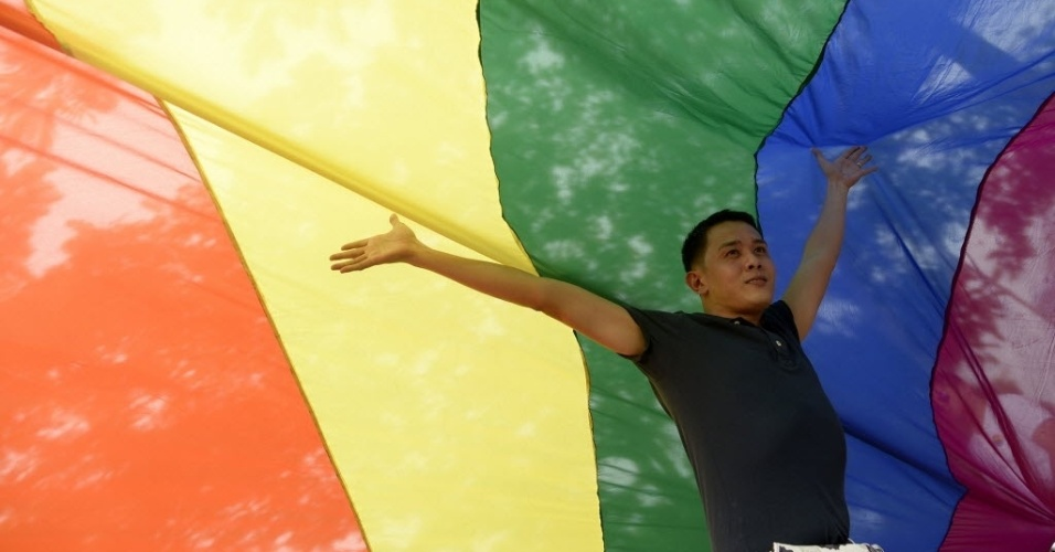 27.jun.2015 - Participante posa para foto embaixo de bandeira durante marcha do orgulho gay em Manila, nas Filipinas