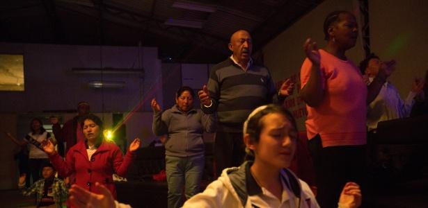 Fiéis rezam enquanto uma banda toca em um encontro de católicos carismáticos da comunidade Jovens do Espírito Santo, em um prédio próximo à igreja San Jose Obrero, em Quito, no Equador