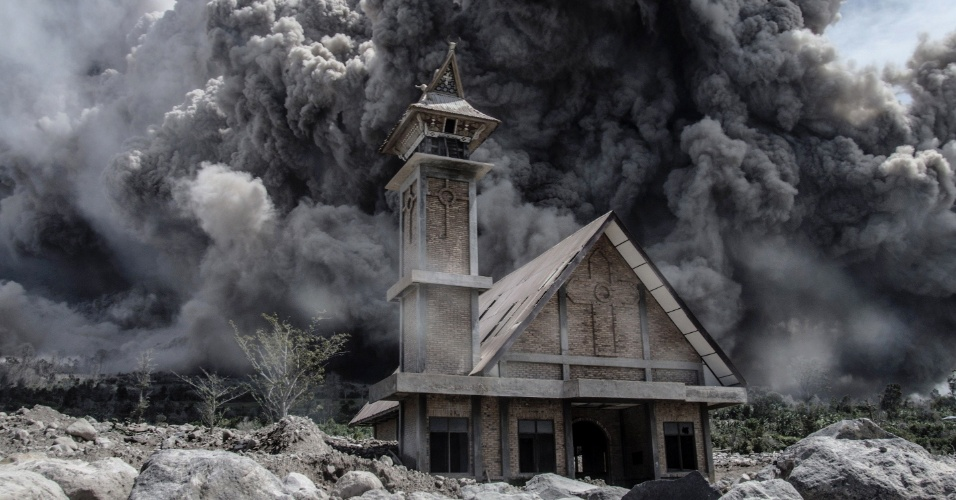 19.jun.2015 - Cinzas de vulcão Sinabung encobrem o céu sobre igreja abandonada na cidade de Karo, na província indonésia de Sumatra do Norte, nesta sexta-feira (19). O monte Sinabung voltou à atividade neste ano depois de quase dois anos de 'descanso', levando à retirada de mais de 10 mil pessoas e à declaração de alerta máximo pelo governo da Indonésia