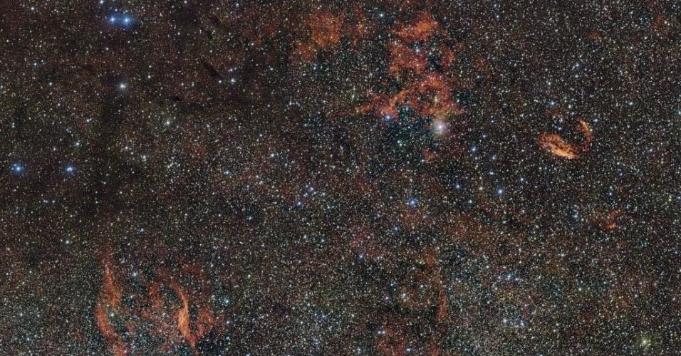 2.mar.2016 - Esta foto disponibilizada pelo Observatório Europeu do Sul e tirada por um telescópio no Chile pode ajudar a solucionar o mistério de como surgem as estrelas. Astros maiores e mais maciços que nosso Sol queimam seu material e exibem cor azulada. Neste processo, emitem radiação ultravioleta, que faz brilhar em vermelho as nuvens de gás e poeira, como visto na foto. A mais brilhante das nuvens está na constelação de Norma, estudada por cientistas para descobrir como se formam estrelas