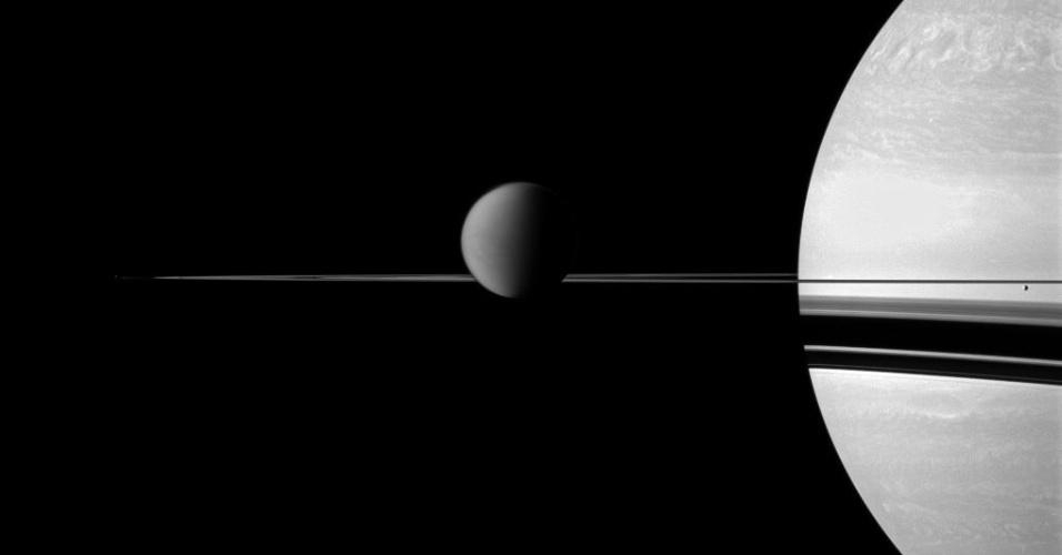 27.ago.2015 - Saturno tem mais 50 luas, sendo Titã a maior dela. Assim como a Europa de Júpiter, existe a possibilidade de que Titã abrigue vida, pois foram encontrados água e hidrocarbonetos em sua estrutura. Nesta foto feita pela Cassini em 2011, Titã está no centro da imagem