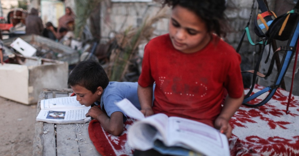 19.abr.2016 - A palestina Hamza Farawana, de 9 anos, lê ao lado do seu irmão Ola no sul da Faixa de Gaza