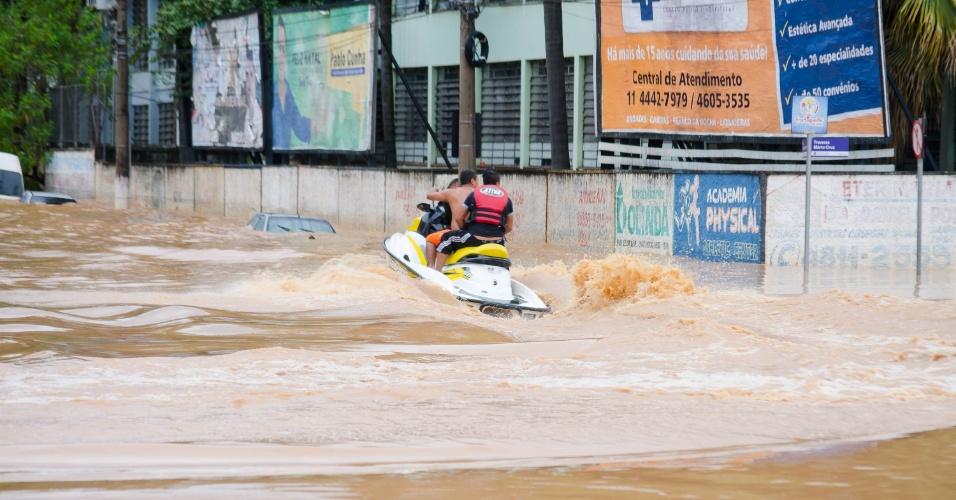 11.mar.2016 - Homens andam de jet ski em rua alagada no centro de Franco da Rocha (SP)