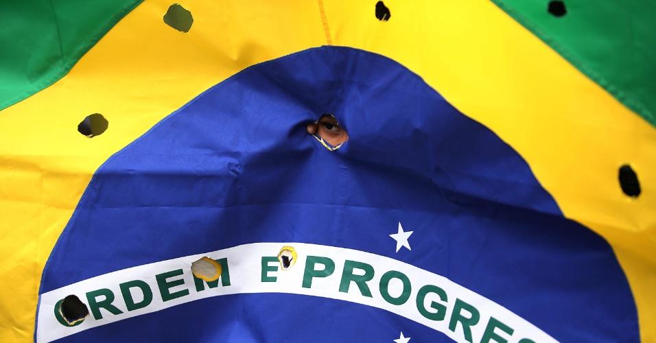 30.nov.2015 - Bandeira do Brasil furada, em alusão a marcas de tiros, foi uma das formas de protesto durante o enterro de cinco jovens assassinados por PMs no Rio de Janeiro. O veículo onde os rapazes estavam foi atingido por mais de 50 disparos de fuzil