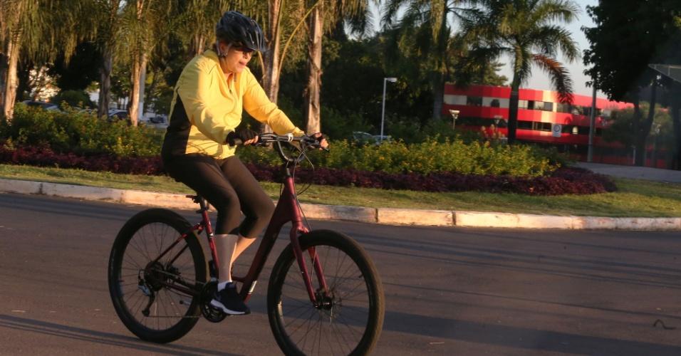 22.mar.2016 - A presidente Dilma Rousseff passa de bicicleta em frente ao hotel Royal Tulip (ao fundo), em Brasília, na manhã em que a Polícia Federal realizava buscas no local na 26ª fase da Operação Lava Jato, batizada de