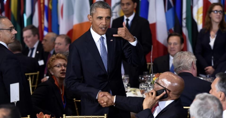 28.set.2015 - Presidente americano, Barack Obama, brinca com o seu colega sul-africano, Jacob Zuma, por estar ao telefone durante o almoço oficial da Assembleia-Geral da ONU