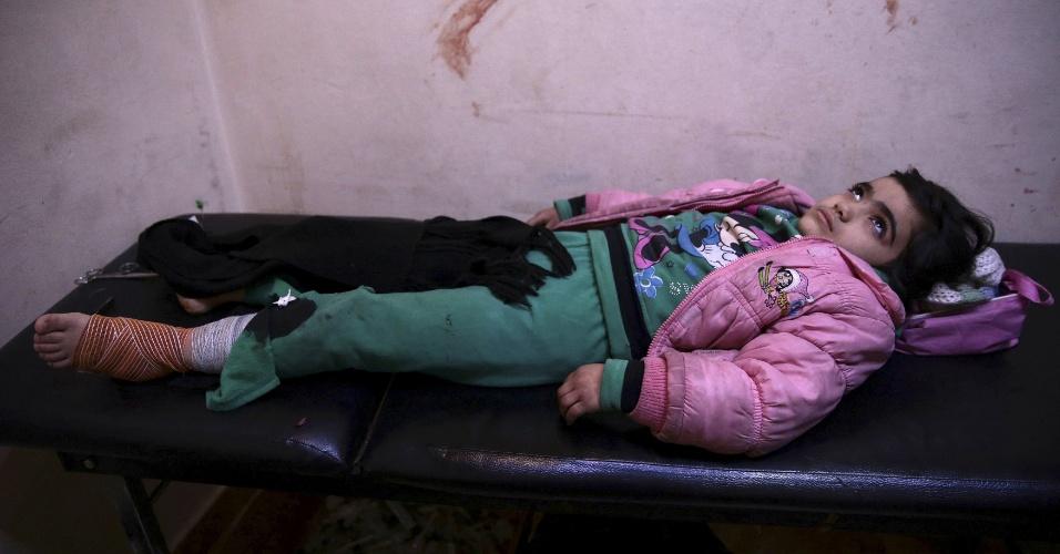 Ferida no pé, menina repousa após atendimento no hospital improvisado em Douma, cidade síria controlada pelos rebeldes e alvo de ataques do Exército de Bashar al-Assad