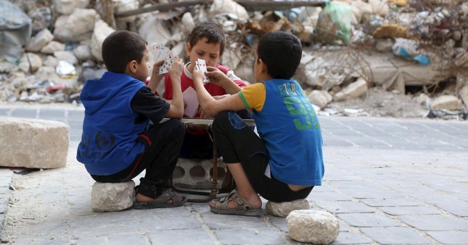 18.out.2015 - Crianças brincam com cartas de baralho em meio aos escombros na cidade de Aleppo, na Síria. A região é algo das ofensivas russas e sírias contra os opositores do presidente Bashar al-Assad