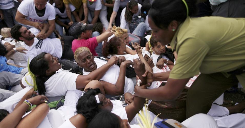 20.mar.2016 - Políciais femininas prender uma das integrantes das Damas de Branco, grupo dissidente que luta pela libertação de presos políticos em Cuba, durante protesto em Havana horas antes da chegada de Obama