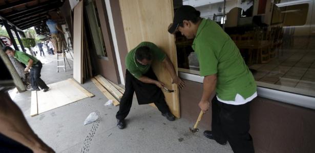 Funcionários de restaurante cobrem janelas com placas de madeira, enquanto o furacão Patricia se aproxima, no balneário de Puerto Vallarta, no Mèxico
