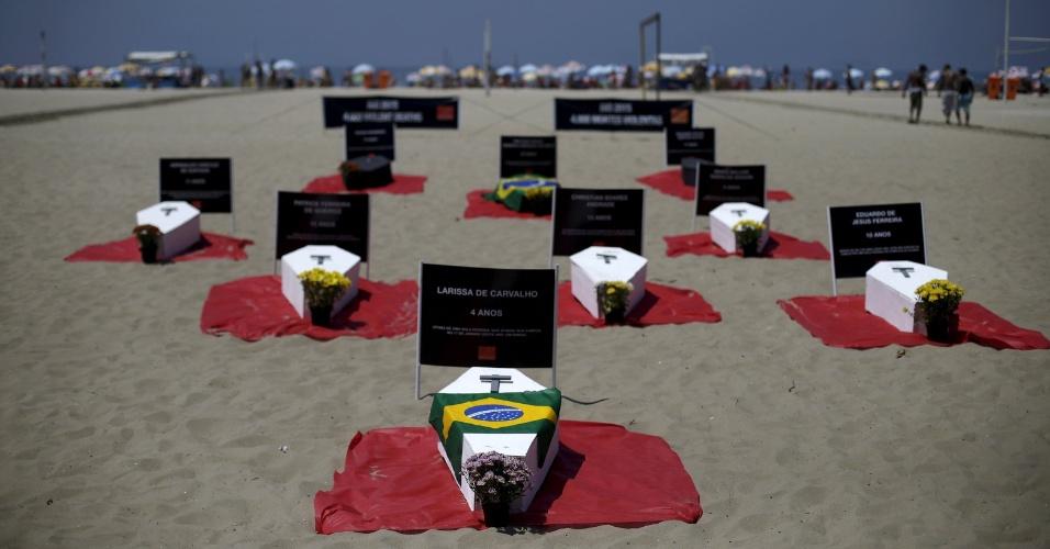 11.out.2015 - Caixões representando vítimas da violência foram colocados na praia de Copacabana durante protesto da ONG Rio de Paz, no Rio de Janeiro. Segundo os organizadores, o Estado do Rio já registrou 4.000 mortes violentas em 2015