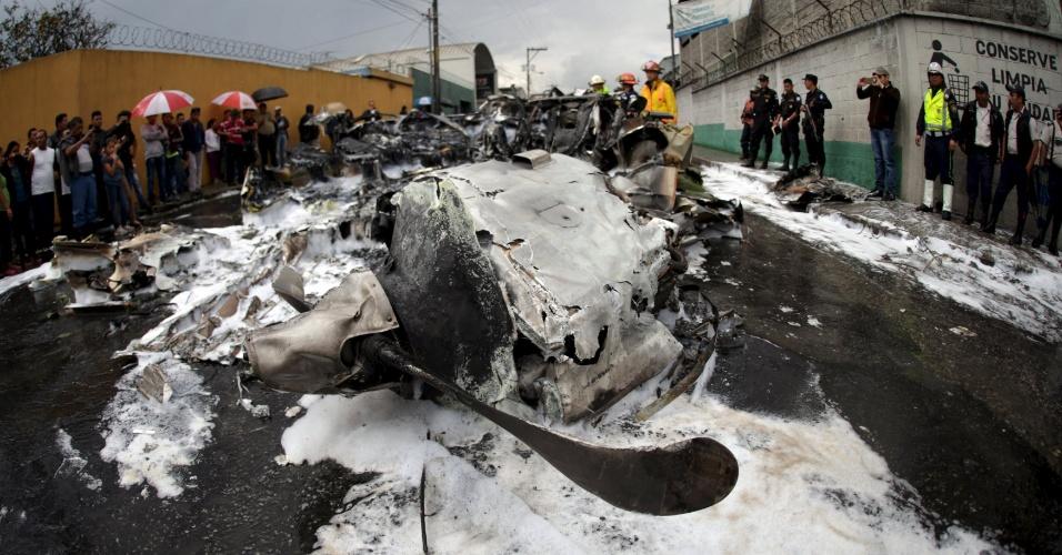 21.nov.2015 - Equipes de resgate e policiais observam os restos de um acidente de avião ocorrido na Cidade da Guatemala. A aeronave de pequeno porte caiu logo após decolar do aeroporto internacional La Aurora, com dois tripulantes a bordo, que foram levados ao hospital com ferimentos leves