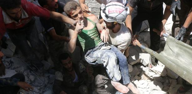 Voluntários resgatam menino de escombros após bombardeio em Aleppo em 25 de julho