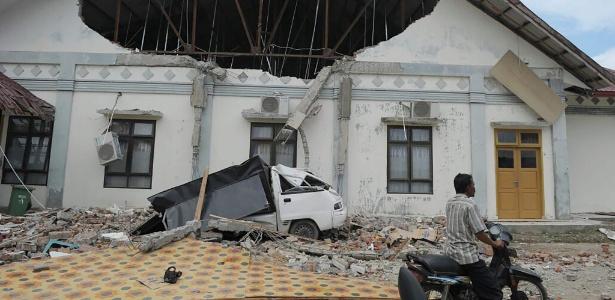 Homem passa diante de prédio destruído pelo terremoto em Pidie Jaya, na província de Aceh, Indonésia