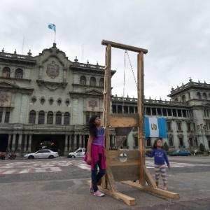 7.set.2015 - Crianças posam para foto ao lado de guilhotina colocada como protesto diante de palácio presencial na Cidade da Guatemala