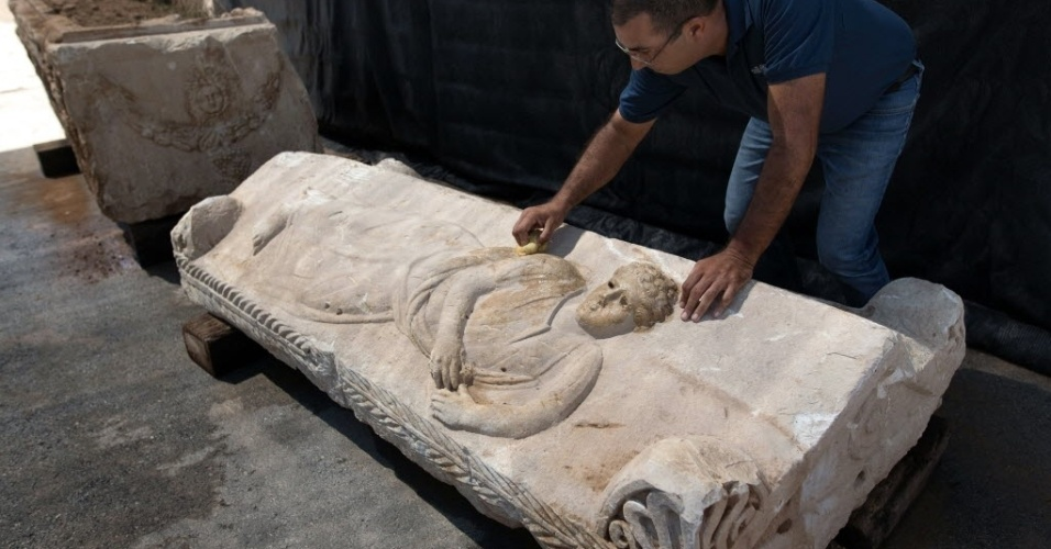 3.set.2015 - Diretor da Autoridade de Antiguidades de Israel (IAA), Saar Ganor, limpa a tampa de um sarcófago original da era romana adornada com a escultura de um jovem, em um depósito da cidade de Bet Shemesh. O sarcófago, com idade estimada em 1.800 anos e requintadas esculturas de figuras mitológicas greco-romanas, foi encontrado por trabalhadores em um canteiro de obras na cidade costeira israelense de Ashkelon. Durante a retirada, os trabalhadores acabaram danificando a relíquia