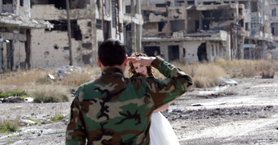 6.fev.2016 - Os recém-casados Nada Merhi, 18, e Hassan Youssef, 27, posam para fotos em meio a área devastada de Homs, na Síria. O casal decidiu fazer o resgitro do casamento em meio as ruínas da cidade destruída pela guerra, para mostrar que mesmo no mais hostil dos ambientes, a vida é mais forte que a morte