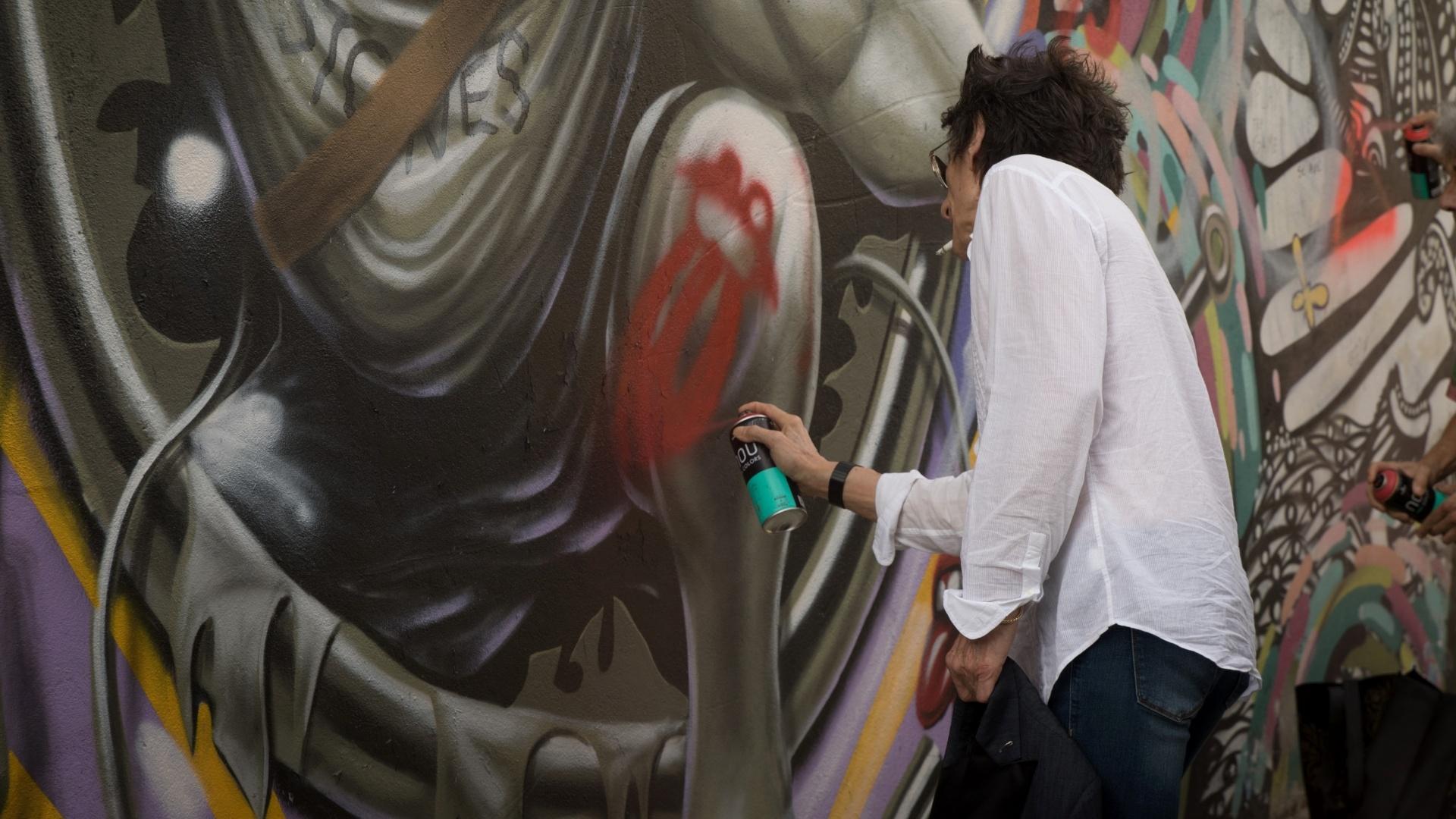 23.fev.2016 - Guitarrista dos Rolling Stones, Ron Wood aproveitou a passagem da banda por São Paulo para fazer uma intervenção artística em parede grafitada do Beco do Batman, na Vila Madalena, zona oeste da cidade. O grupo de rock toca na capital paulista nesta quarta (24) e sábado (27)