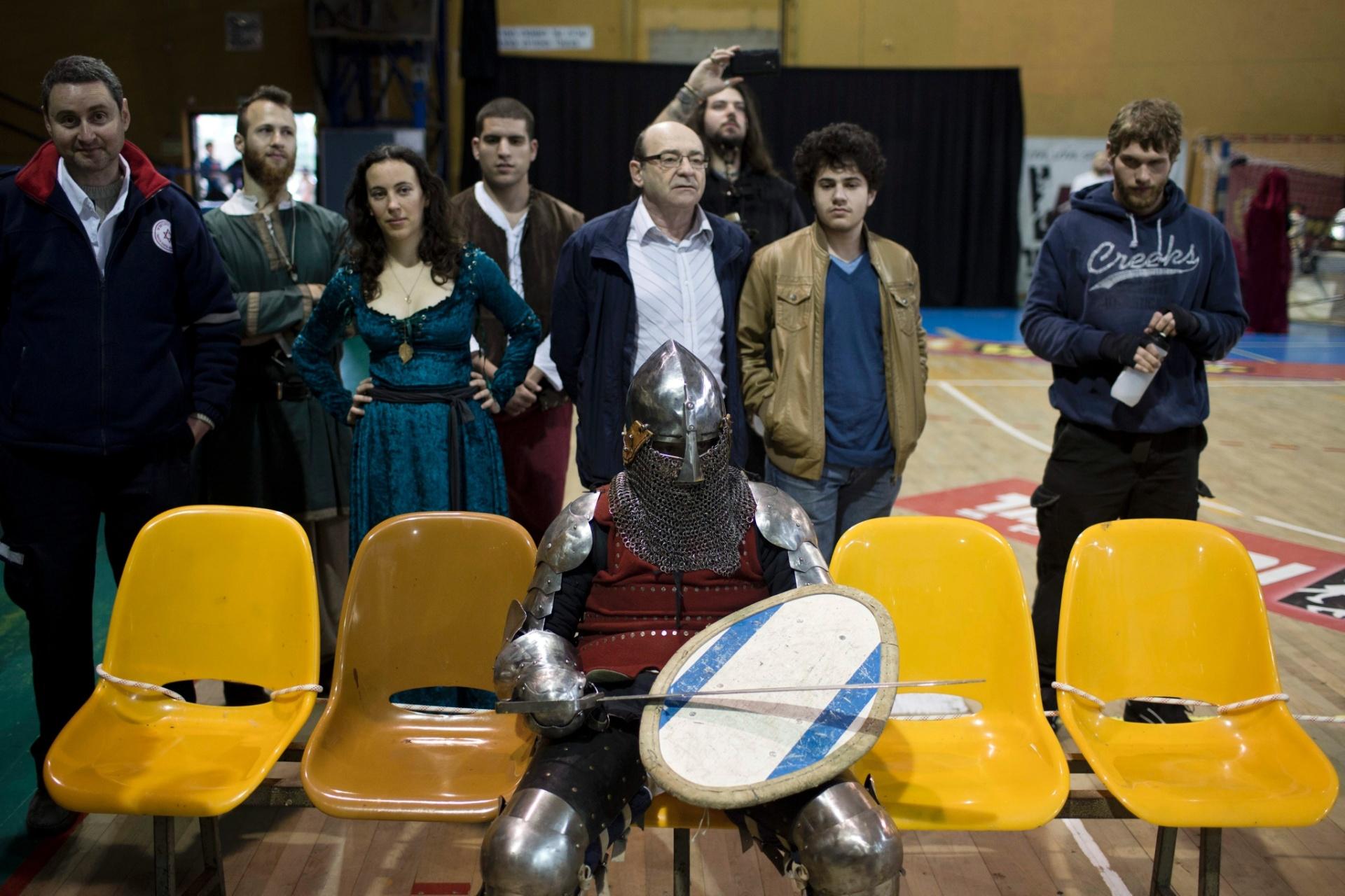 23.jan.2016 - O evento, logicamente, leva a cenas curiosas como esta: uma pessoa vestida de cavaleiro aguarda sua vez sentada em um banco, junto a pessoas comuns e outras com trajes históricos