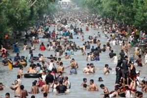 Paquistaneses se refrescam em rio em um canal durante a onda de calor no país