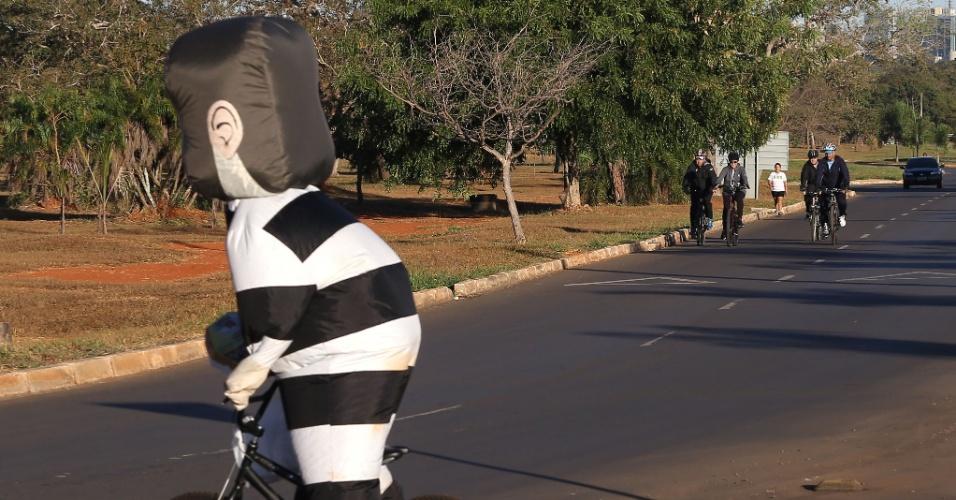 13.jun.2016 - Em seu tradicional passeio matinal de bicicleta, a presidente afastada, Dilma Rousseff, foi surpreendida por um manifestante vestido de pixuleco montado em uma pequena bicicleta em Brasília (DF). O manifestante tentou se aproximar da petista, que estava acompanhada por dois seguranças e por seu personal trainer, mas foi contido por uma barreira de carros