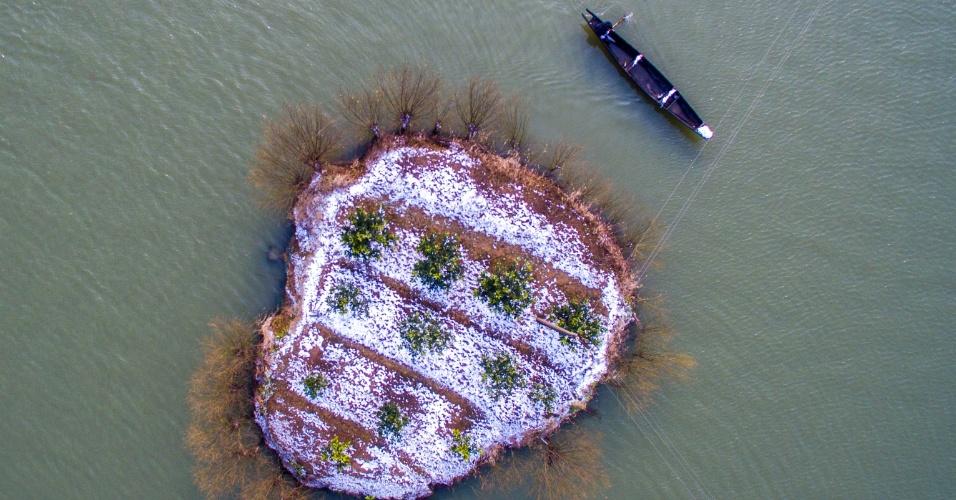 23.jan.2016 - Barco navega ao lado de ilha coberta de neve em rio próximo ao vilarejo de Dingshanhe, na região chinesa de Hangzhou, no leste do país. Apesar de não ser tão forte quanto nos EUA, uma forte onda de frio trouxe bastante neve para o leste da China