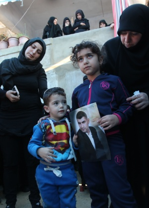 Ali e Malak (à dir.) seguram a foto do pai, Adel Termos, morto ao se jogar diante de um homem-bomba em Beirute