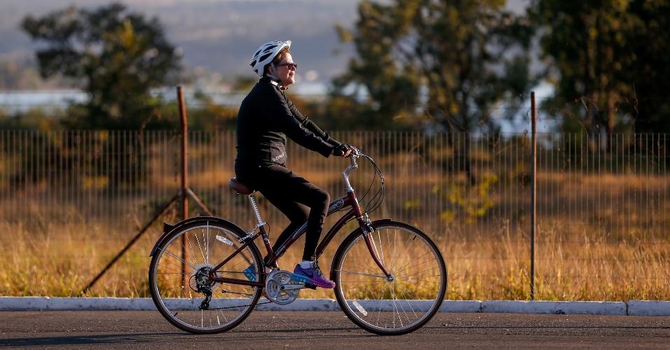 23.jul.2015 - A presidente Dilma Rousseff anda de bicicleta acompanhada de seguranças e seu treinador nos arredores do Palácio da Alvorada, em Brasília, no início da manhã