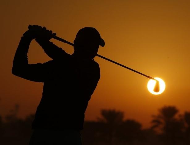 21.jan.2016 - ... acerta a bola e acompanha ela com o olhar. A silhueta da foto é do golfista irlandês Rory McIlroy. A bola incandecente é, na verdade, o sol. A bolinha verdadeira não está visível por causa da sombra. A foto foi feita no Golf Club Abu Dhabi, nos Emirados Árabes
