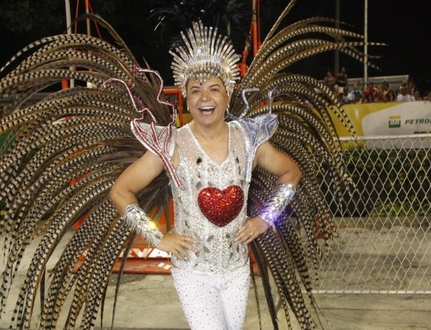 16.fev.2013 - David Brazil mostra sua fantasia com plumas e um coração vermelho antes do início do desfile das campeãs