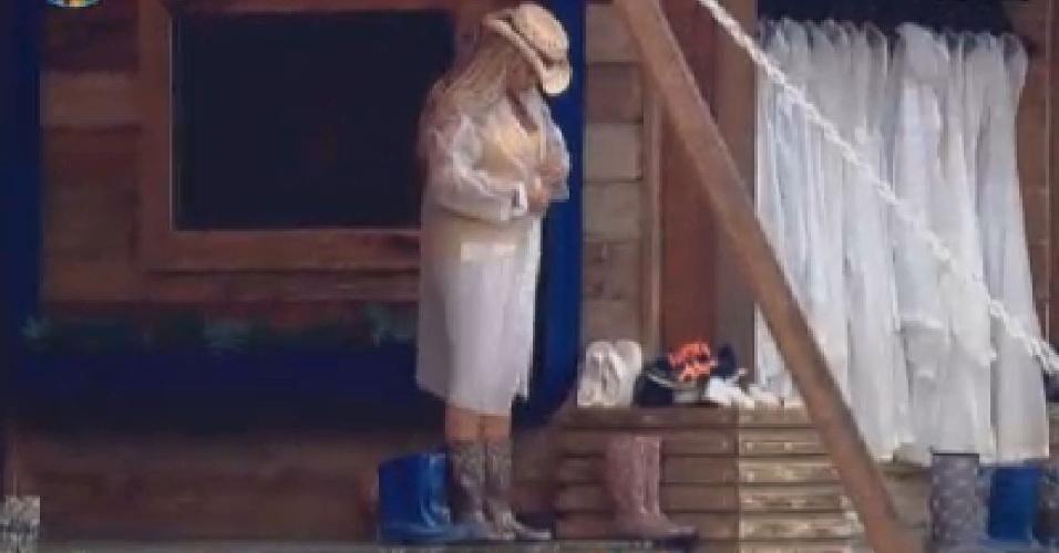 Em dia de garoa em Itu, Ângela Bismarchi veste capa de chuva antes de cuidar dos porcos (19/6/12)