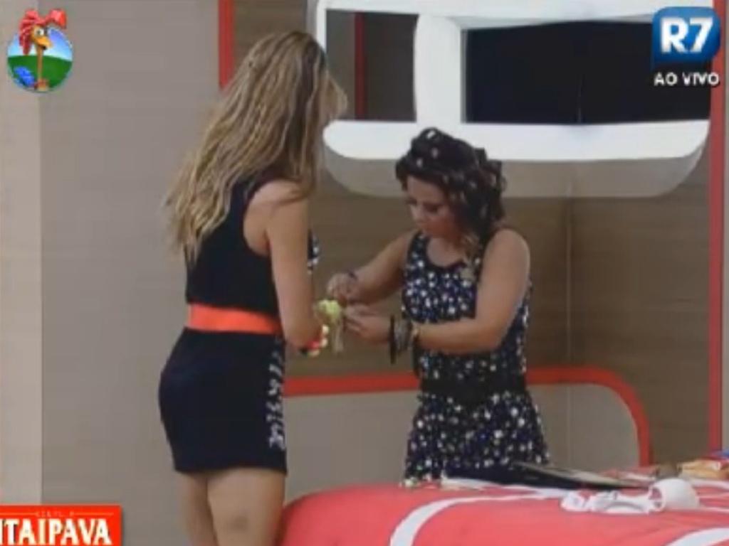 Viviane Araújo (dir.) arruma as pulseiras de Léo Áquilla (esq.) antes da festa com todos os eliminados (27/8/12)