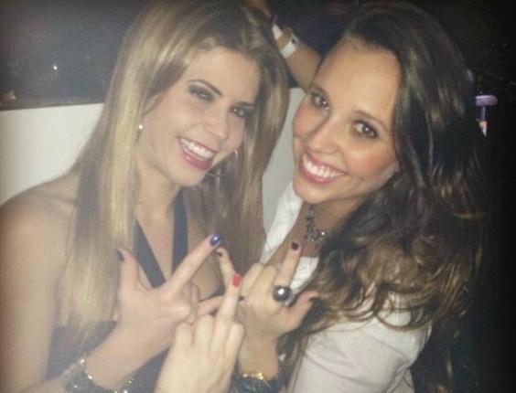 A ex-BBB Claudia Collucci e a peoa Angelis Borges brincam enquanto tiram fotos em balada