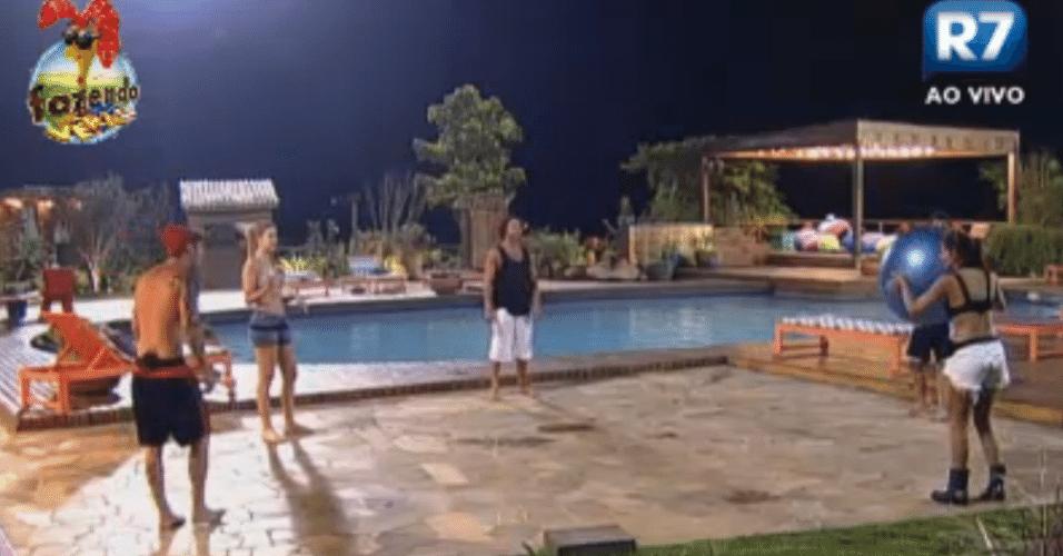 Peões brincam com bola próximos à piscina