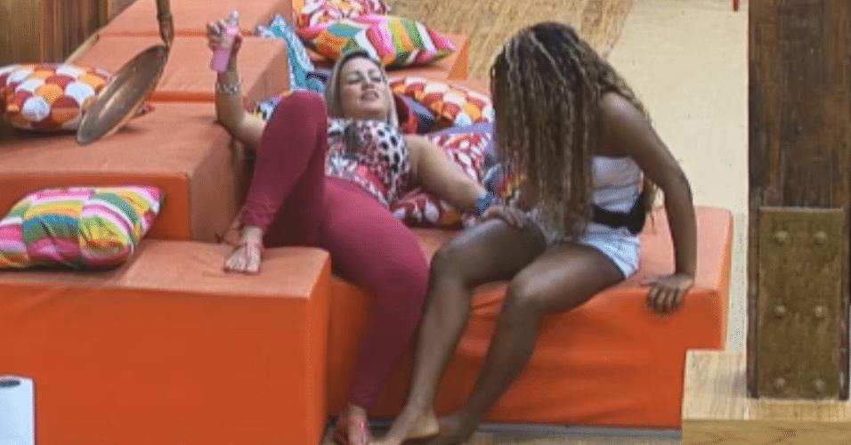 Ísis passa hidratante na perna de Karine